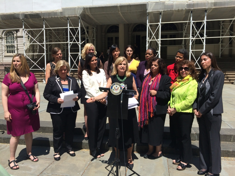 "May 7, 2015—New York City Hall— Assembly Member Seawright stands in support of Congresswoman Carolyn Maloney's release of a Mother's Day Report that found the economic security of two-thirds of American families depends upon a mother's earnings, and that mothers typically contribute about 40 percent to their families' overall income. The report also found that mothers face a ""Mommy Tax,"" whereby they are paid 3 percent less than women without children. Fathers, alternatively, face a ""Daddy Bonus."" They can expect to earn 14 percent more than their male colleagues who don't have children."