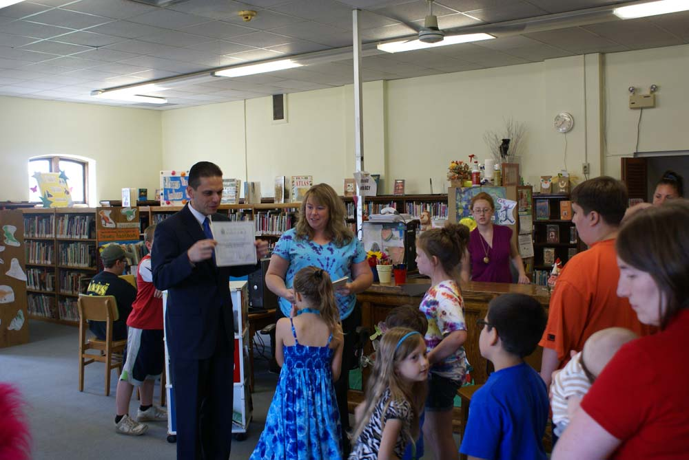 Assemblyman Santabarbara awards certificates to children who completed the Amsterdam Free Library's Summer Reading Program.