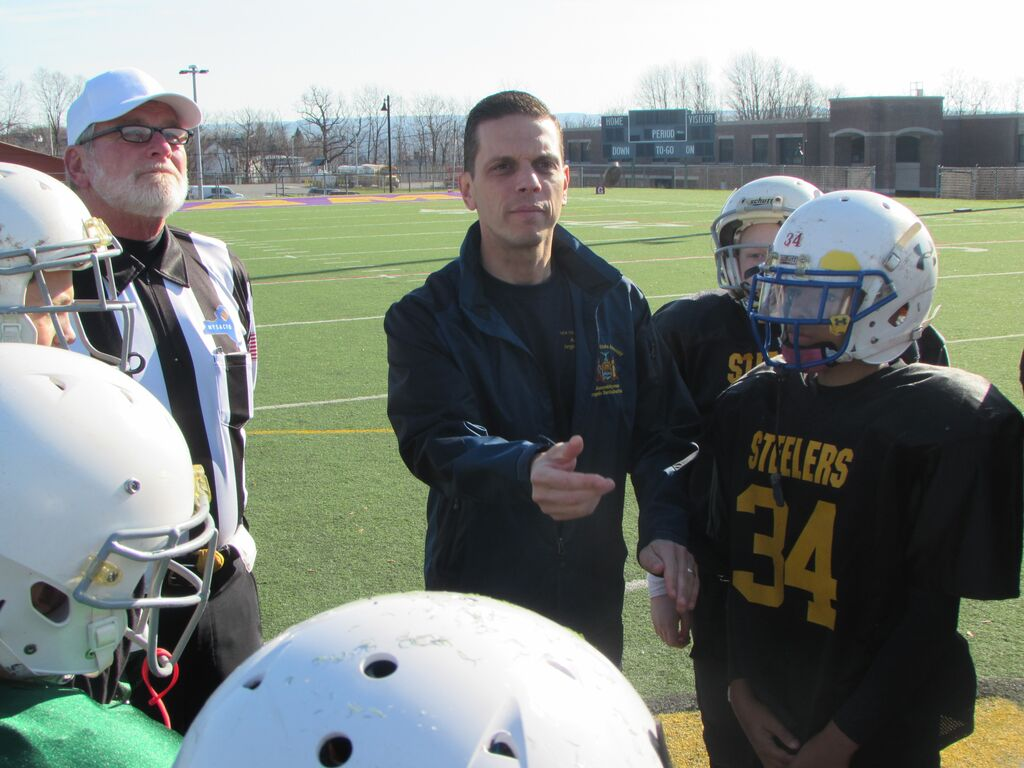 Assemblyman Angelo Santabarbara performs the coin toss before the Amsterdam Little Giants' Super Bowl after presenting the youth football league with new helmets and a $2,500 check for the purpose of buying additional safety equipment. 11/15/2015